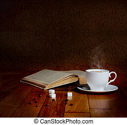 Hot cup of fresh coffee on the wooden table and a stack of books to read