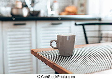 Hot cup of tea or coffee on wood table in kitchen background