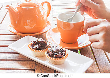 Hot cup of white tea and crispy chocolate tarts