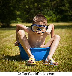 Hot day - Boy wearing swimming mask sitting in a washbowl on...