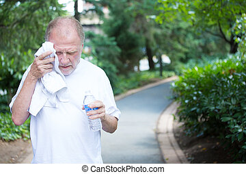 Closeup portrait, old gentleman in white shirt having difficulties with extreme heat, high temperature, wiping sweat from face, very tired, isolated green trees paved road background