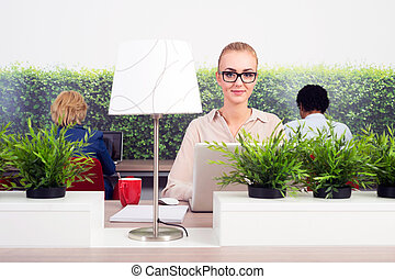 Hot desking - Portrait of smiling business woman working in ...