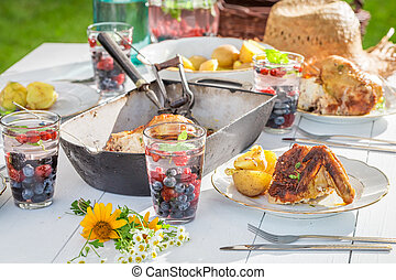 Hot dinner with chicken and potatoes served in the garden