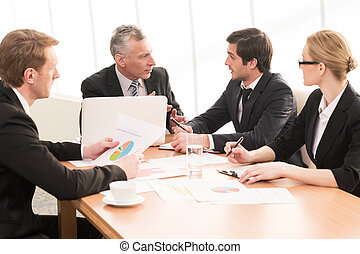 Hot discussion. Four business people in formalwear discussing something while sitting together at the meeting