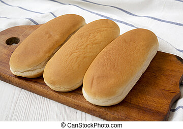 Hot dog buns on wooden board, side view. Closeup.