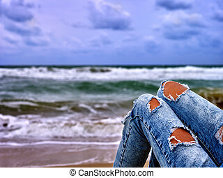 Hot dog leg selfie girl sitting near ocean with waves.