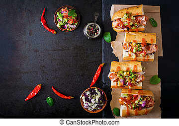 Hot dog - sandwich with Mexican salsa on dark background....