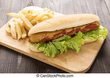 Hot dog with french fries on wooden background.