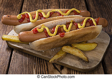 Hot Dog with ketchup and mustard (close-up shot) on wooden...