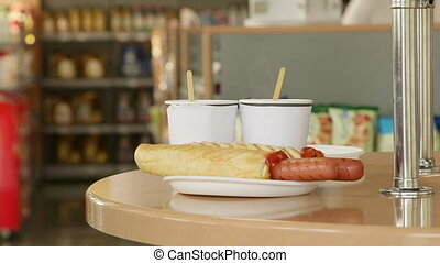 Hot dogs and cups of coffee on the table in convenience...