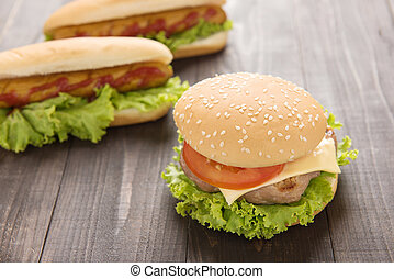 Hot dogs, hamburgers on the wooden background.