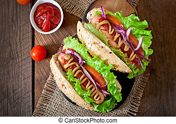 Hot Dogs with ketchup mustard and lettuce on wooden ...