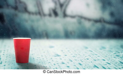 hot drink evaporating smoke on snowing melting ice - red cup...