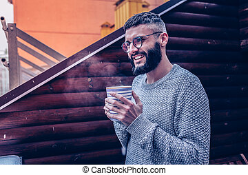 Happy cheerful man holding a cup with tea