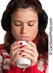 Young woman drinking a hot drink from a white mug, isolated in a white background