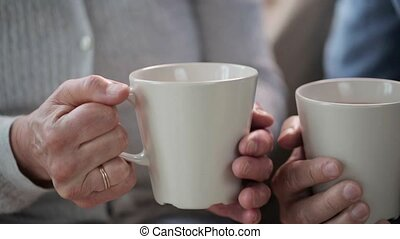 senior couple hands with cups of tea - hot drinks, leisure...