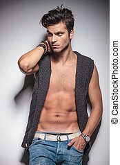 hot fashion man looking away while leaning on a wall