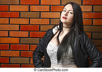 Hot girl against brick wall