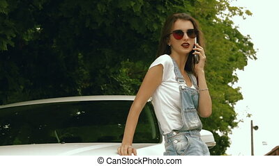 hot girl standing near machines and talking on the phone