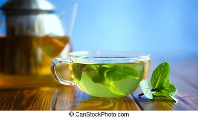 hot green tea with fresh mint on a blue background