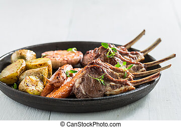 Hot grilled ribs of lamb with garlic and vegetables