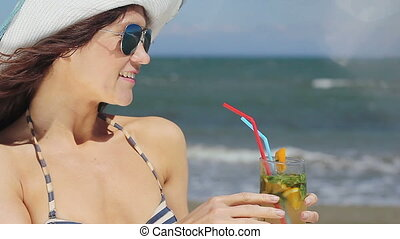 Hot lady enjoying exotic cocktail, long drink, vacation at luxury resort's beach