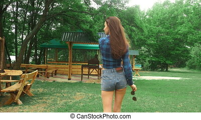 hot Lady in short denim shorts walks outdoors
