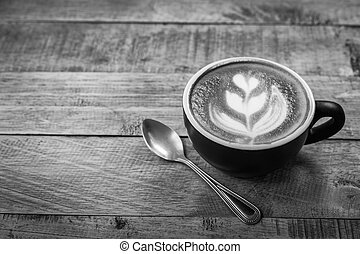 Hot latte art coffee cup on table, vintage and retro style black and white tone
