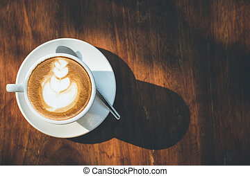 Hot latte coffee in white cup on wooden table with copy...