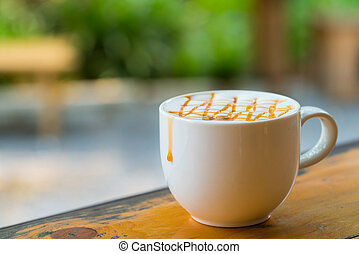 Hot Macchiato coffee with caramel in white cup on wood table