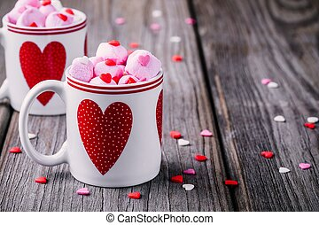 Hot milk with pink marshmallow in mugs with hearts for Valentine's day