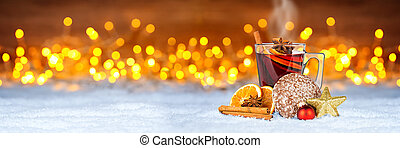hot mulled spiced red wine in glass mug with gingerbread orange slice christmas market panorama background