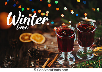 hot mulled wine in glasses with Christmas decor with the inscription Winter Time