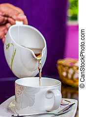 tea pouring into glass cup