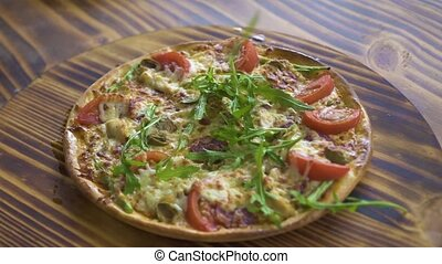 Hot pizza with fresh herbs on wooden table. Original italian...