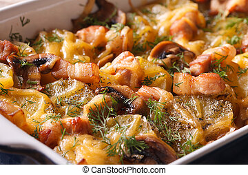 Hot potato with bacon, mushrooms and cheese in baking dish