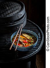 Hot Red Curry soup in black bowl with chopsticks