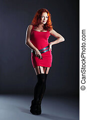 Hot red-haired woman posing in studio