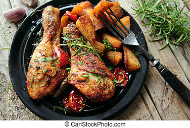 Hot roasted chicken legs with fried potatoes