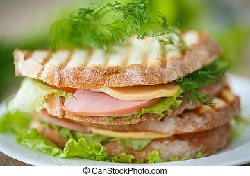 sandwich with sausage, cheese and herbs