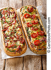 Hot sandwiches with bacon, mushrooms, tomatoes and cheese close-up on parchment. vertical