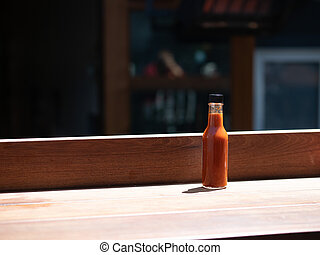 Hot sauce bottle sitting on table in outdoor dining area at restaurant