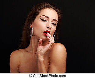 Hot sexy exciting woman with hand near red lips on black...