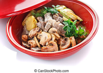 hot slices of pork with sauce with vegetables on the grill zucchini, eggplant, mushrooms, potatoes, peppers, tomatoes, parsley on a black plate
