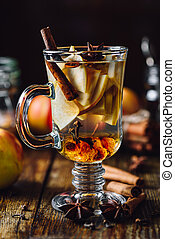 Hot Spiced Beverage with Sliced Apples and Different Condiment.