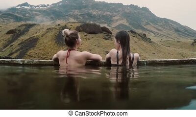 Hot spring geothermal spa in Iceland. Two traveling woman...