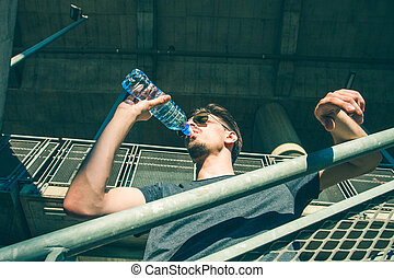 hot summer day young man drinking water from bottle