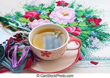 Hot tea and cross stitch placed on the table