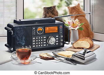 Hot tea, bread and oil on a table with the radio receiver...