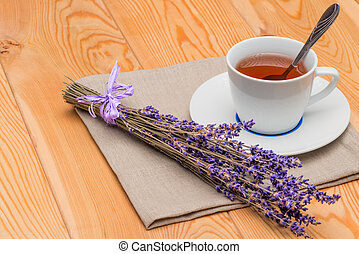 hot tea in a cup with lavender on a linen napkin close-up